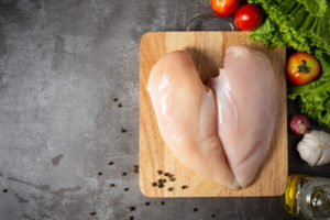 Фото - Raw chicken breasts on wooden cutting board.