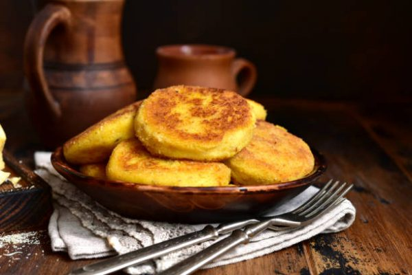 Fried potato patties with cheese on a rustic background.